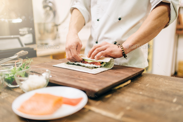 Male cook making seafood, asian kitchen - Stock Photo - Images