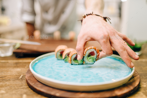 Male person cooking sushi rolls on wooden table - Stock Photo - Images