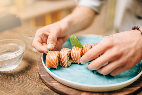 Male person cooking sushi rolls, japanese food - Stock Photo - Images