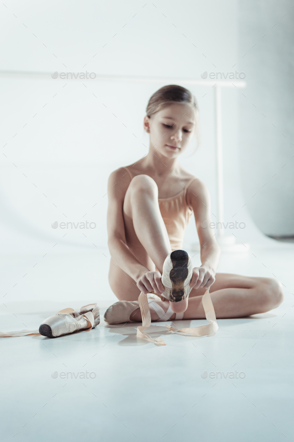 Beautiful little ballerina in blue dress for dancing puting on foot pointe shoes - Stock Photo - Images