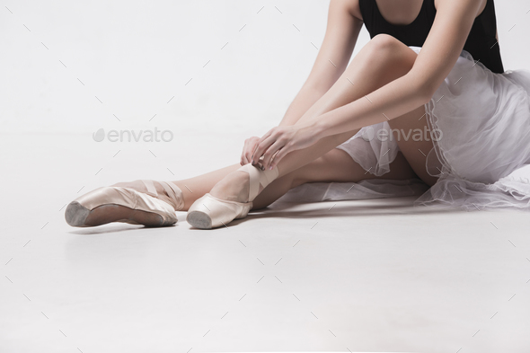 Ballerina dancer sitting down with her legs crossed - Stock Photo - Images