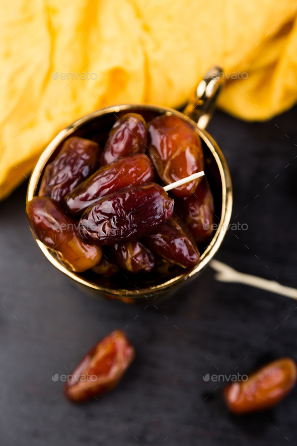 Dry fruit dates in golden cup near slate black heart. - Stock Photo - Images