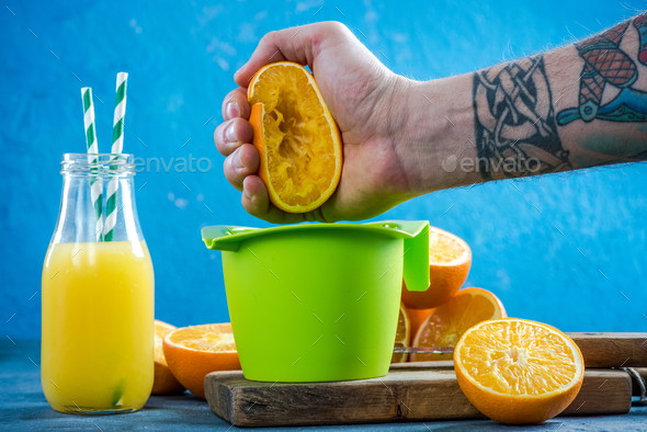 Hand squeezing orange halves for juice - Stock Photo - Images