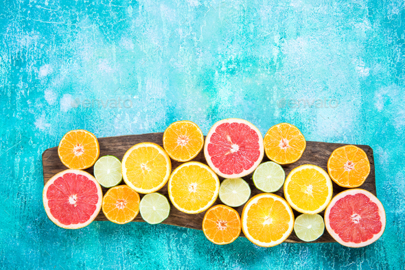 Citrus fruits halves on wooden board - Stock Photo - Images