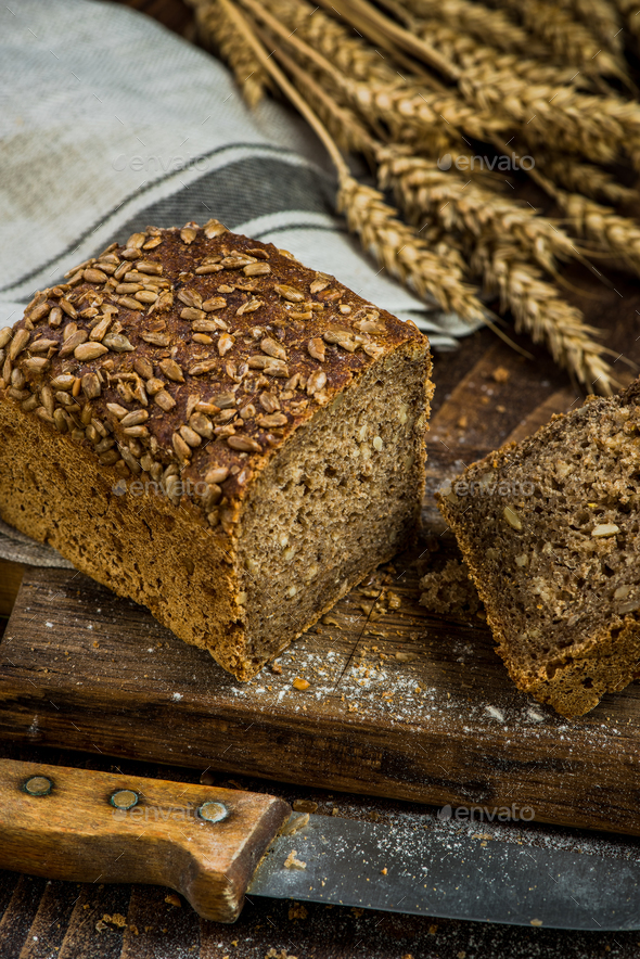 Wholegrain bread with seeds sliced on board - Stock Photo - Images