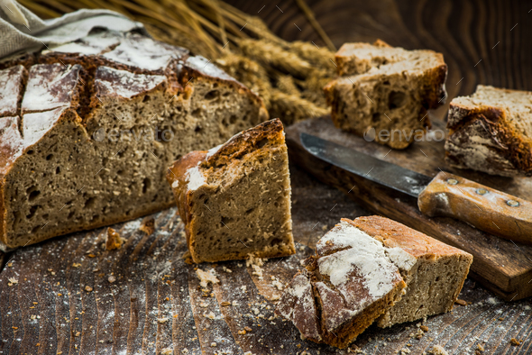 Sharing pieces of freshly baked bread loaf - Stock Photo - Images