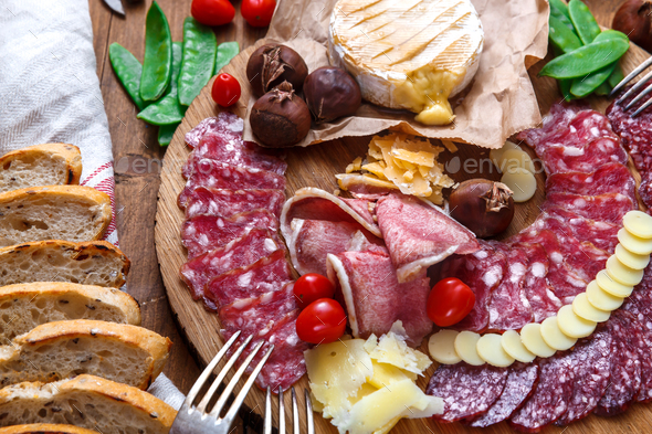 Delisious snacks on wooden board: sausages, bread, cheese, chestnuts and beer. Close view. - Stock Photo - Images