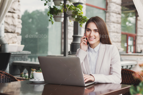Young businesswoman looking at front, talking on phone - Stock Photo - Images