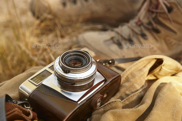 Vintage camera with hiking boots on the ground. Travel background - Stock Photo - Images
