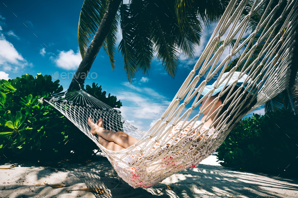 Woman relaxing in the shade of palms on a hammock. - Stock Photo - Images