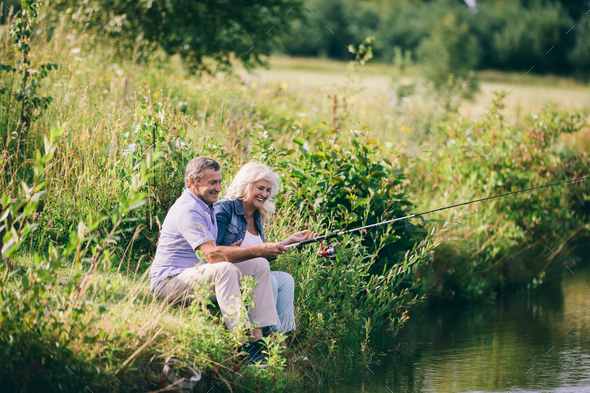 Senior couple fishing by the water. - Stock Photo - Images