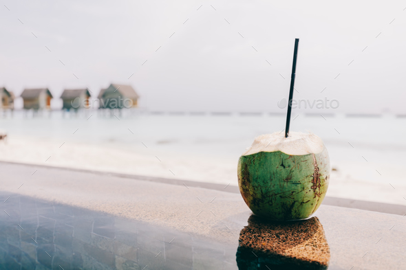 Coconut with a straw standing. Ocean view - Stock Photo - Images