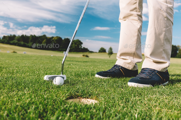 Man trying to put a golfball into the hole. - Stock Photo - Images