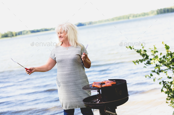 Senior woman barbecuing by the lake. - Stock Photo - Images