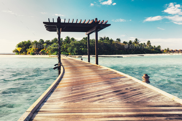 Wooden jetty with arch leading to a tropical island - Stock Photo - Images