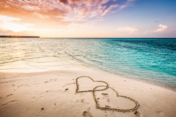 Two hearts drawn on a sandy beach by the sea. - Stock Photo - Images