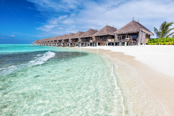 Water villas in a row by the seashore on Maldives Tropical resort - Stock Photo - Images