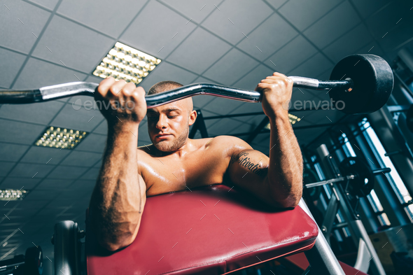 Strong fit man exercising on a gym. - Stock Photo - Images