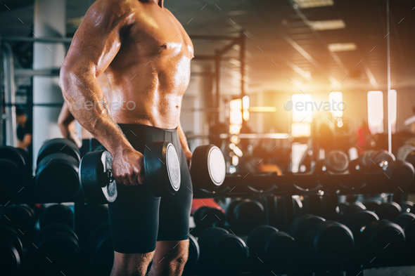 Muscular man holding dumbbels in a gym. - Stock Photo - Images