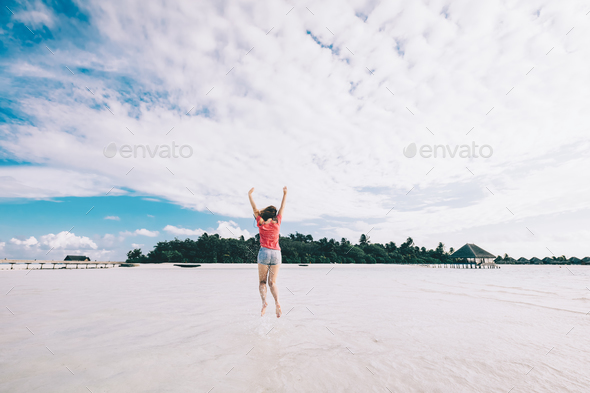 Girl jumping on a sandy beach. Fun time on Maldives - Stock Photo - Images