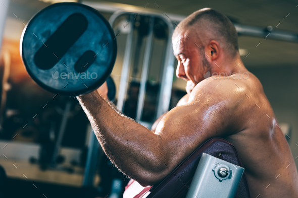 Man lifting weights in a gym - Stock Photo - Images