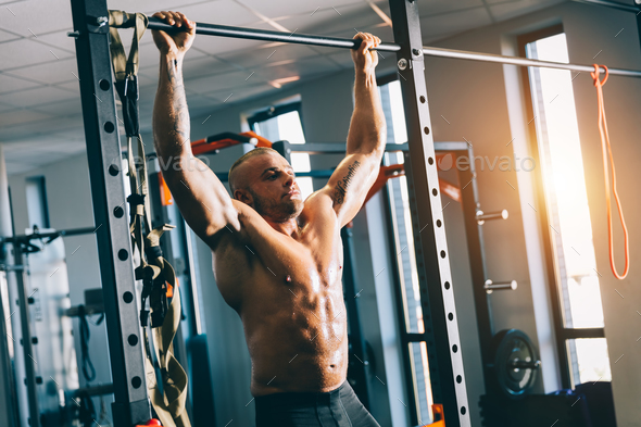 Muscular man doing pull-ups in a gym. - Stock Photo - Images