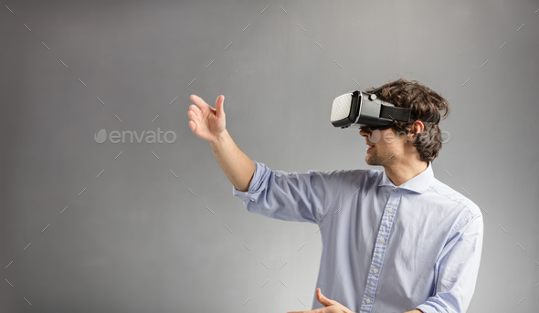 Young man playing in virtual reality goggles - Stock Photo - Images