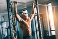 Muscular man doing pull-ups in a gym. - PhotoDune Item for Sale