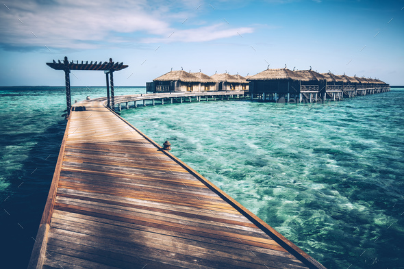 Wooden jetty with arch on a clean turquoise ocean water. - Stock Photo - Images