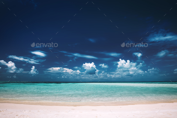 Sandy beach, clear see-through sea and blue sky. - Stock Photo - Images