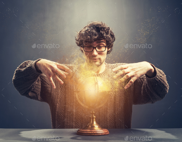 Young man gazing at the glowing crystal ball. - Stock Photo - Images