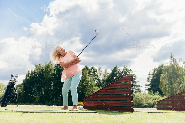 Senior active woman playing on a golf course. - Stock Photo - Images