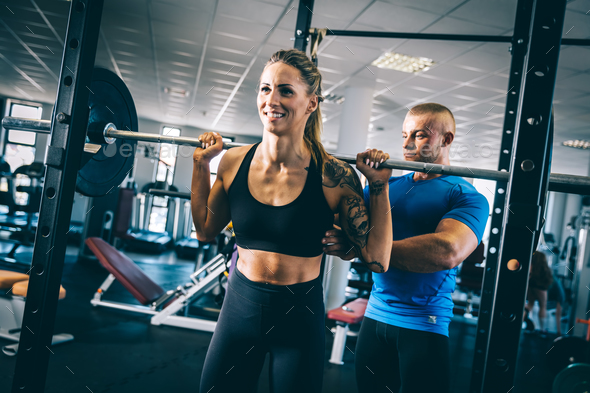 Man instructing a woman on a gym. - Stock Photo - Images