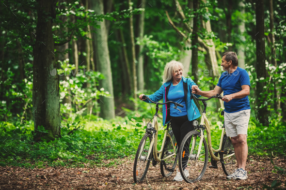 Retired couple walking with bikes in the forest. - Stock Photo - Images