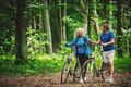 Retired couple walking with bikes in the forest. - PhotoDune Item for Sale