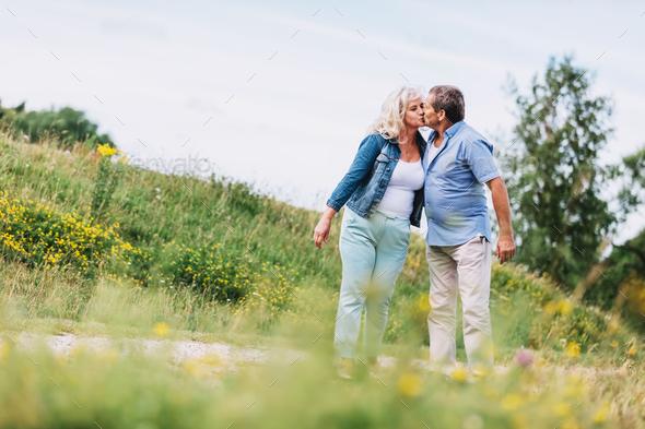 Old couple kissing on a walk. - Stock Photo - Images