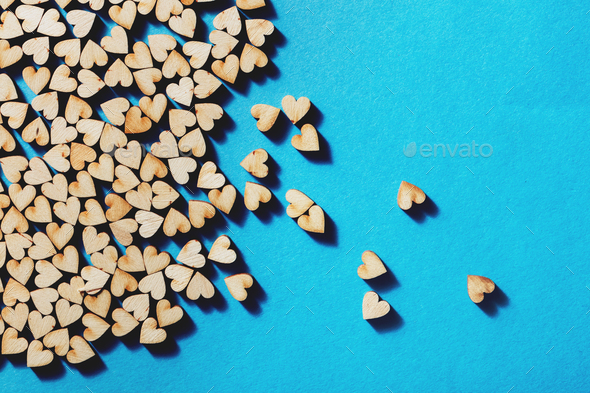 Wooden hearts laying on blue background. - Stock Photo - Images