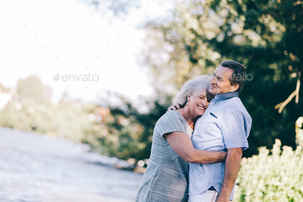 Senior woman hugging her husband - Stock Photo - Images