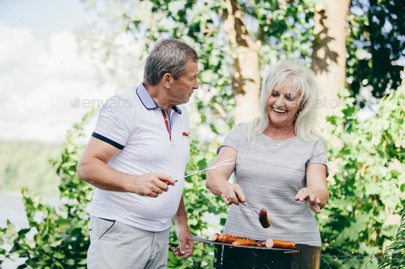 Happy elderly couple barbequing together. - Stock Photo - Images