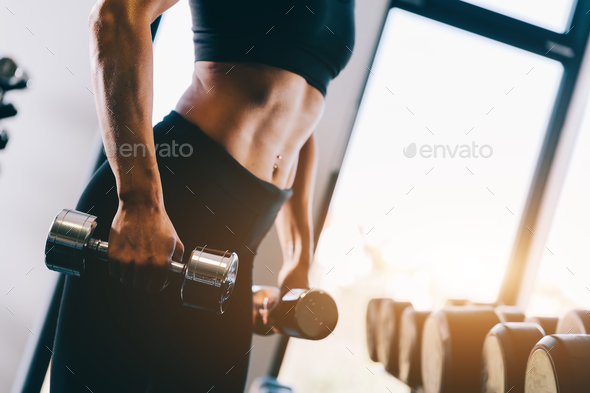 Fit body of a woman holding dumbbells. - Stock Photo - Images
