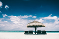 Straw umbrella and sunbeds on a sandy beach - PhotoDune Item for Sale