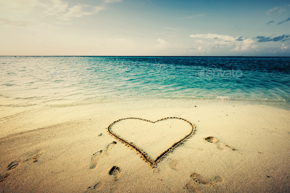 Heart shape drawn on a sand at the seaside. - Stock Photo - Images