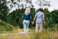 Old couple holding hands on a walk. - PhotoDune Item for Sale
