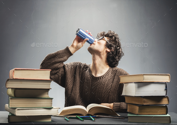 Young man studying and drinking energy drink. - Stock Photo - Images