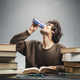 Young man studying and drinking energy drink. - PhotoDune Item for Sale