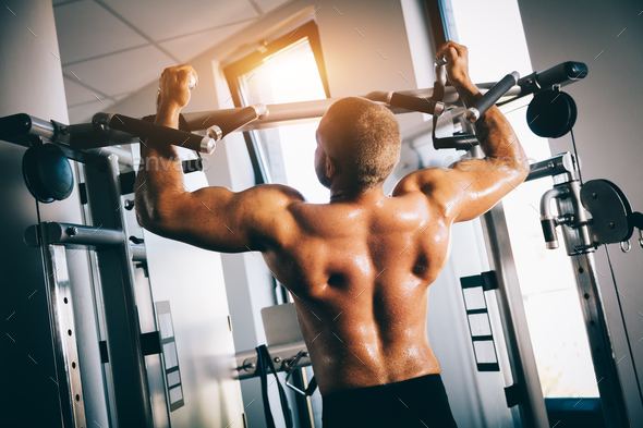 Strong man exercising in a gym. - Stock Photo - Images