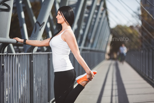 City workout. Beautiful woman training in an urban setting - Stock Photo - Images
