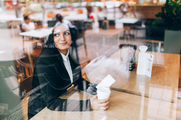 Business woman with smart phone sitting in a cafe - Stock Photo - Images