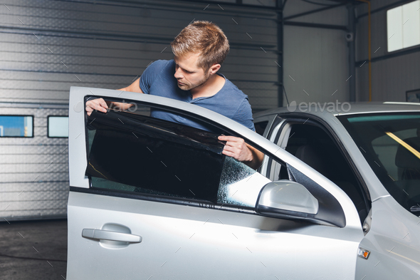 Applying tinting foil onto a car window - Stock Photo - Images
