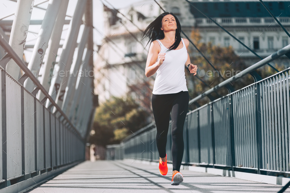 City workout. Beautiful woman running in an urban setting - Stock Photo - Images